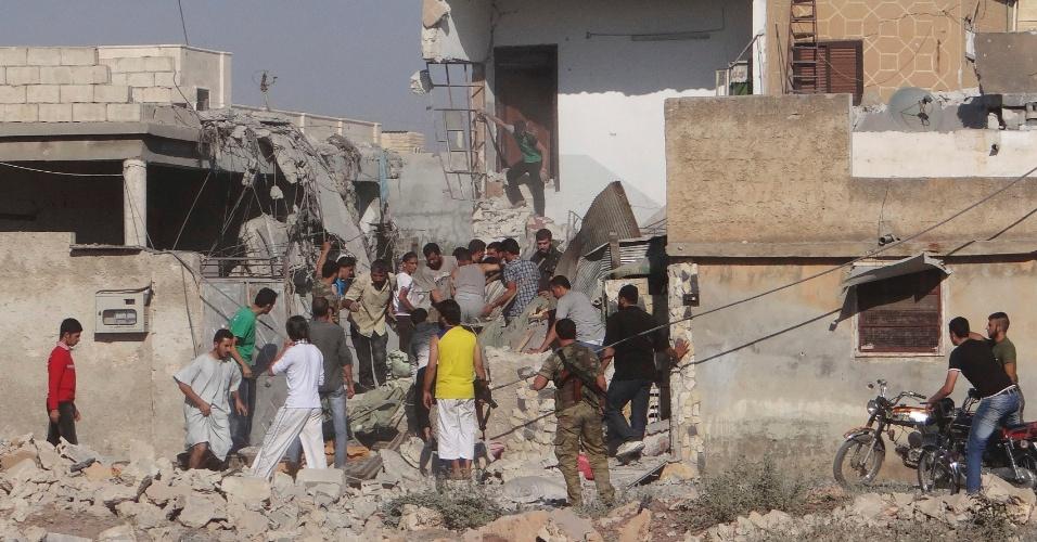 16.set.2012 - Moradores da cidade síria de Saraqib e membros do Exército Livre sírio buscam corpos debaixo de escombros de uma casa que foi destruída durante bombardeio aéreo