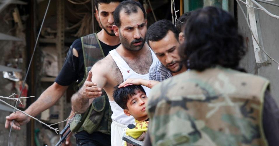 16.set.2012 - Moradores e membros do Exército de Libertação da Síria ajudam garoto que ficou ferido após ataque aéreo em Aleppo