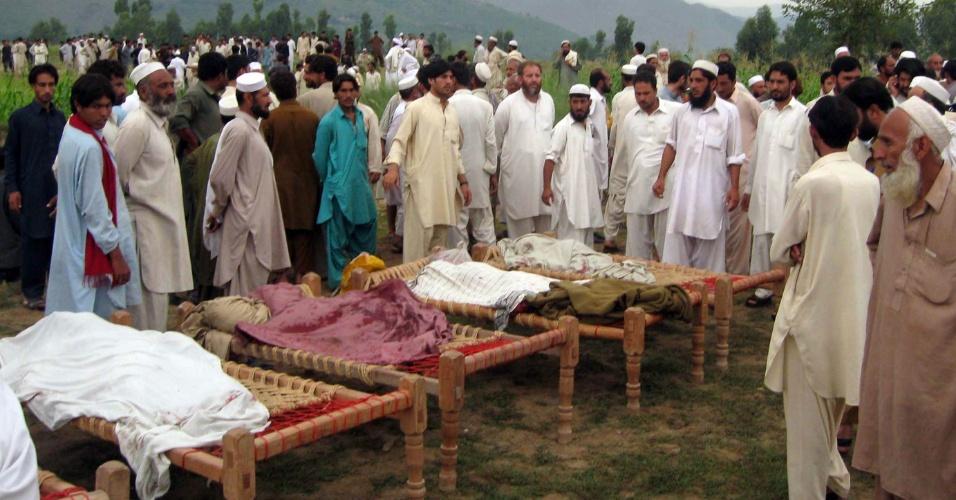 16.set.2012 - Paquistaneses observam restos mortais de vítimas de explosões de bomba na cidade de Jandol