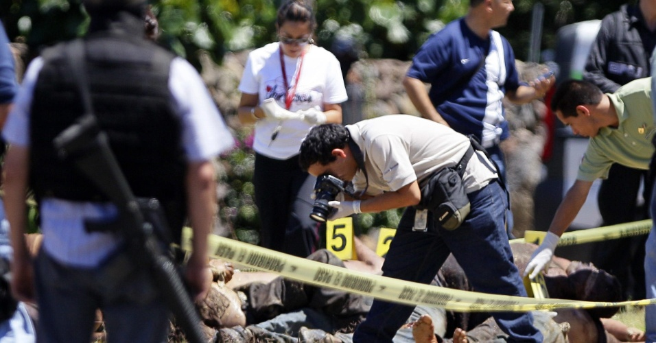 16.set.2012 - Peritos investigam o local onde 17 corpos foram encontrados neste domingo (16), em uma estrada do Estado de Jalisco, no México. Segundo a polícia, a briga entre carteis de drogas procovou as mortes