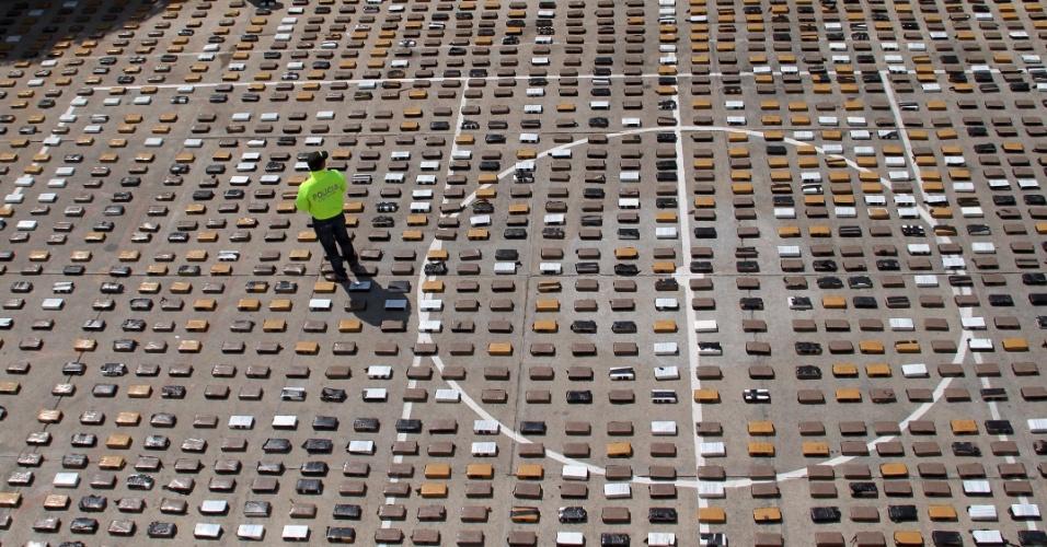 16.set.2012 - Policial colombiano da unidade antidrogas observa pacotes de cocaína apreendidos, em Rioacha, no departamento de Guajira. Foram apreendidas quase duas toneladas da droga, encontradas com traficantes da quadrilha Los Urabeños