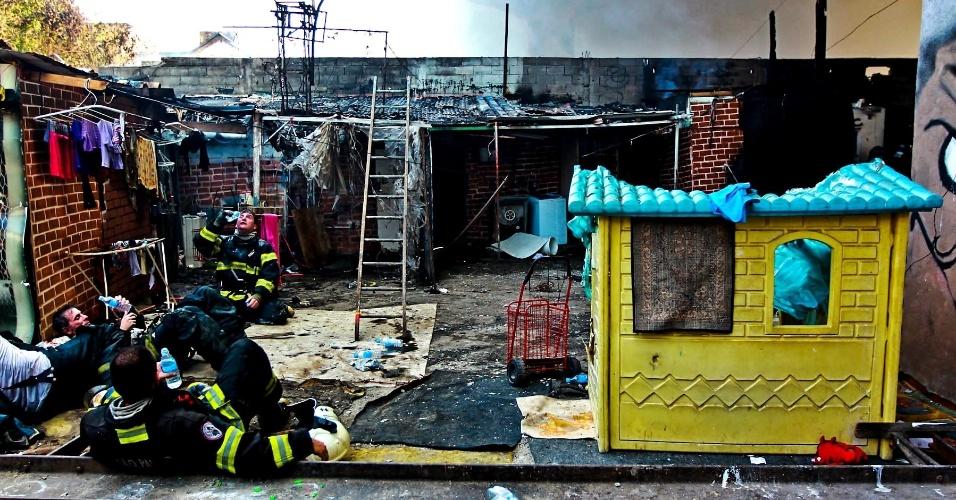17.set.2012 - Bombeiros descansam em barraco destruído por incêndio na favela do Moinho, em São Paulo, nesta segunda-feira (17). O incêndio iniciado por volta das 7h foi controlado cerca de uma hora e meia depois. Uma pessoa morreu e 80 barracos foram destruídos