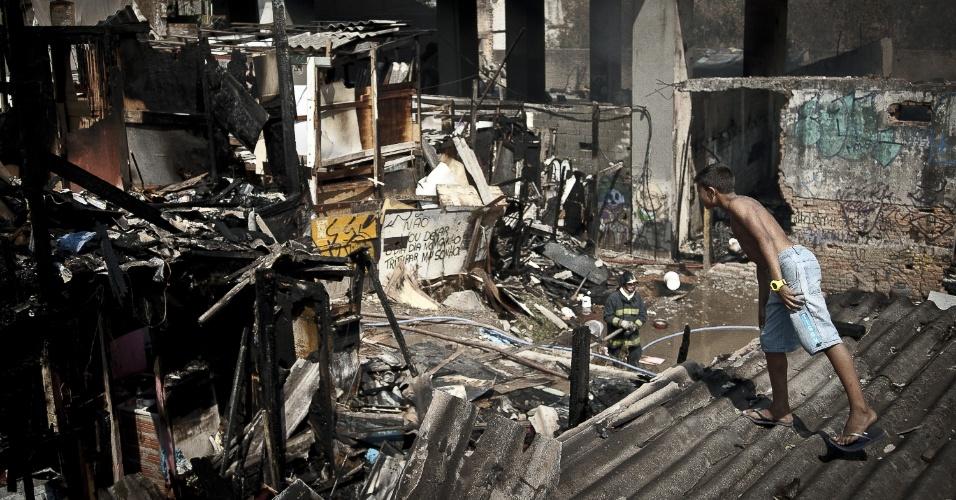 17.set.2012 - Criança observa danos provocados pelo incêndio que atingiu a favela do Moinho, região central de São Paulo, na manhã desta segunda-feira (17). Ao menos uma pessoa morreu e cerca de 50 famílias ficaram desabrigadas. Segundo a polícia, o suspeito de iniciar o fogo na comunidade foi preso e é acusado de ter trancado o parceiro em um barraco em chamas após uma briga