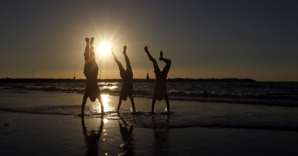 17.set.2012 -  Jovens palestinos brincam em praia da Cidade de Gaza, nesta segunda-feira (17), durante o pôr do sol