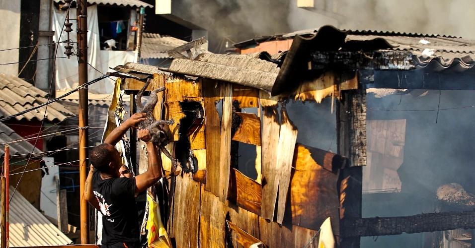 17.set.2012 - Morador da favela do Moinho, em São Paulo, retira gato de um barraco após o incêndio que atingiu o local na manhã desta segunda-feira (17)