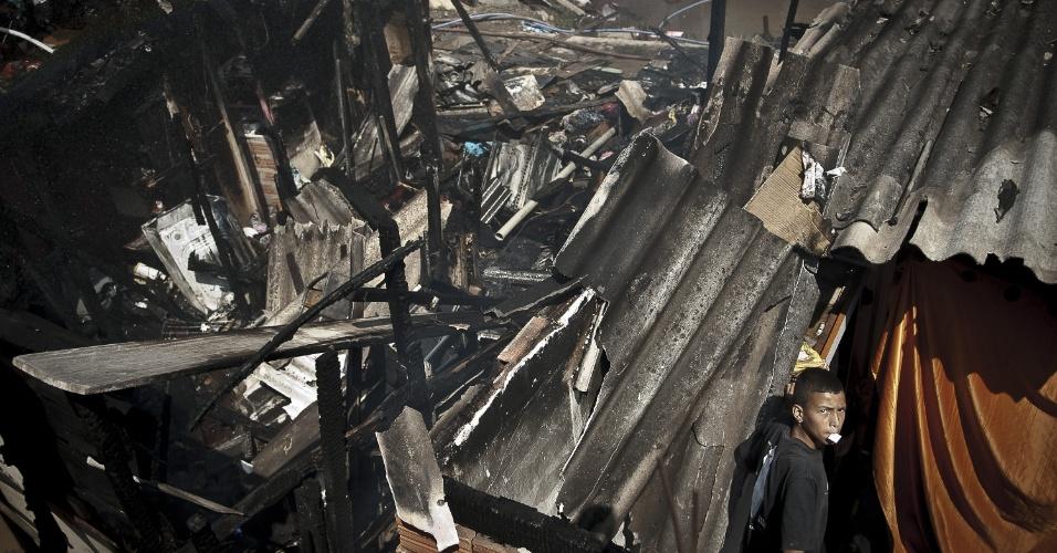 17.set.2012 - Morador tenta recurar pertences que sobreviveram ao incêndio que atingiu a favela do Moinho, região central de São Paulo, na manhã desta segunda-feira (17). Ao menos uma pessoa morreu e cerca de 50 famílias ficaram desabrigadas. Segundo a polícia, o suspeito de iniciar o fogo na comunidade foi preso e é acusado de ter trancado o parceiro em um barraco em chamas após uma briga