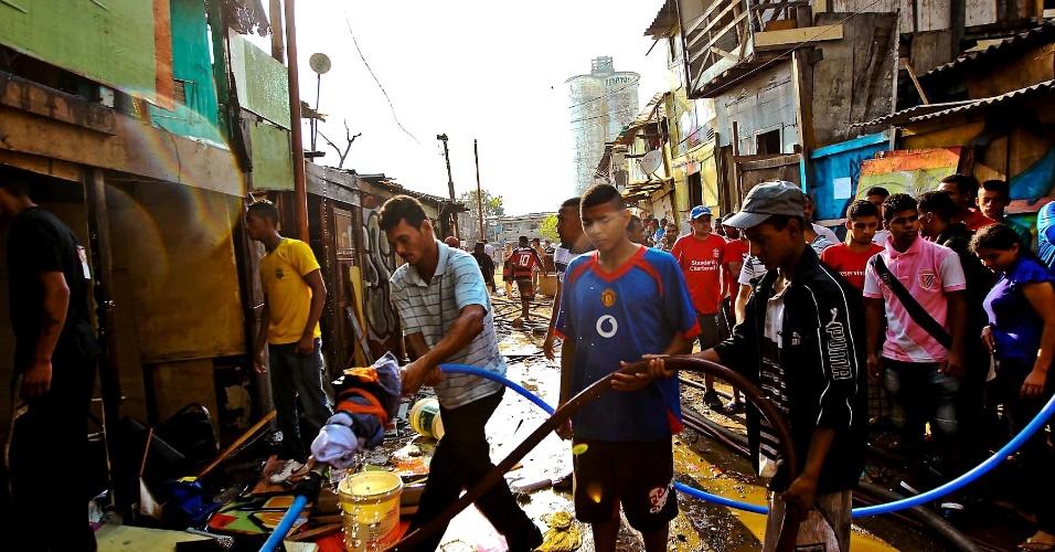 17.set.2012 - Moradores da favela do Moinho, em São Paulo, tentam apagar o incêndio que atingiu o local na manhã desta segunda-feira (17). O fogo foi controlado às 8h30, e uma pessoa morreu, segundo os bombeiros
