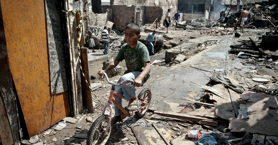 18.set.2012 - Criança anda de bicicleta em meio aos destroços da favela do Moinho, na região central de São Paulo, um dia após o incêndio que provocou a morte de uma pessoa e deixou cerca de 50 famílias desabrigadas. É a segunda vez em menos de um ano que a comunidade, erguida sob o Viaduto Orlando Murgel, é atingida por um incêndio