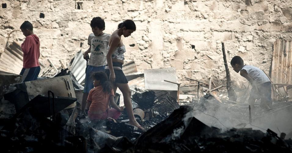 18.set.2012 - Crianças ajudam na limpeza da favela do Moinho, na região central de São Paulo, um dia após o incêndio que provocou a morte de uma pessoa e deixou cerca de 50 famílias desabrigadas. É a segunda vez em menos de um ano que a comunidade, erguida sob o Viaduto Orlando Murgel, é atingida por um incêndio
