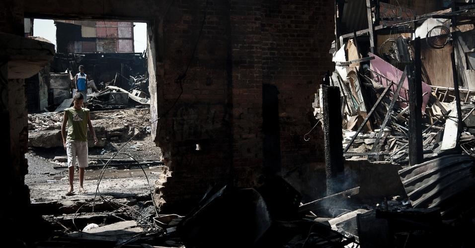 18.set.2012 - Moradores caminham em meio aos destroços da favela do Moinho, na região central de São Paulo, um dia após o incêndio que provocou a morte de uma pessoa e deixou cerca de 50 famílias desabrigadas. É a segunda vez em menos de um ano que a comunidade, erguida sob o Viaduto Orlando Murgel, é atingida por um incêndio