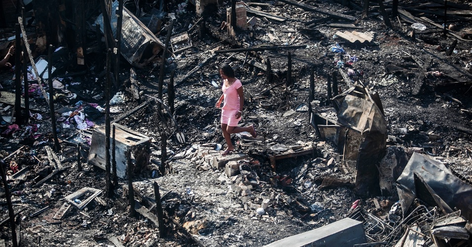 18.set.2012 - Moradora caminha nesta terça-feira (18) por área destruída na favela do Moinho, no centro de São Paulo, após incêndio que atingiu o local ontem (17)