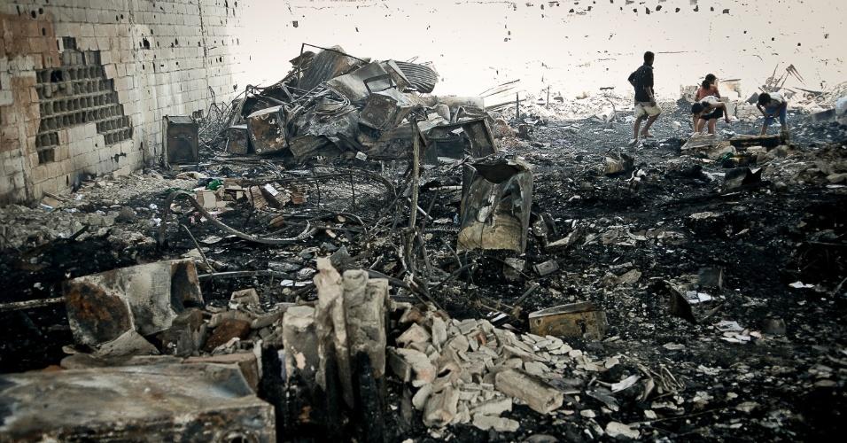 18.set.2012 - Moradores da Favela do Moinho que foram vítimas pela segunda vez em menos de nove meses de um incêndio de grandes proporções já planejam a reconstrução dos barracos no local. Na manhã desta terça-feira, vizinhos ajudavam na retirada do entulho em meio à fumaça