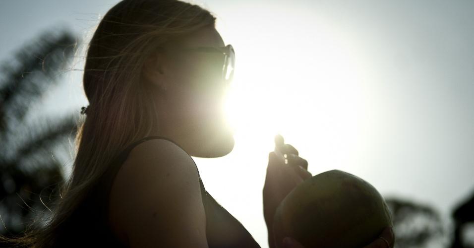 18.set.2012 - Mulher toma água de coco em São Paulo, no dia mais quente do inverno atual