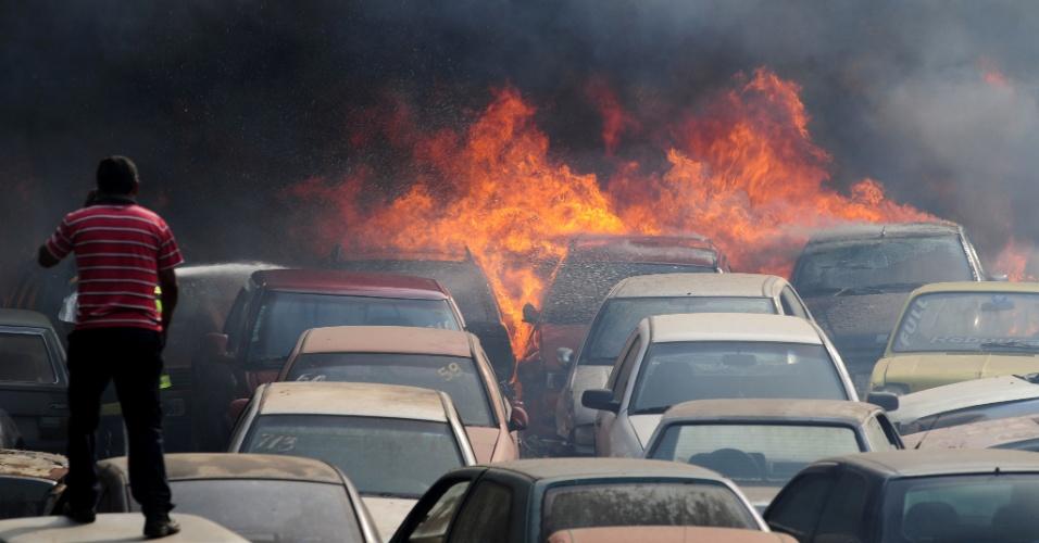19.set.2012 - Bombeiros e funcionários tentam combater um incêndio que atingiu pelo menos 20 carros no pátio Bola Branca, na Vila São Bento, em São José dos Campos (SP)