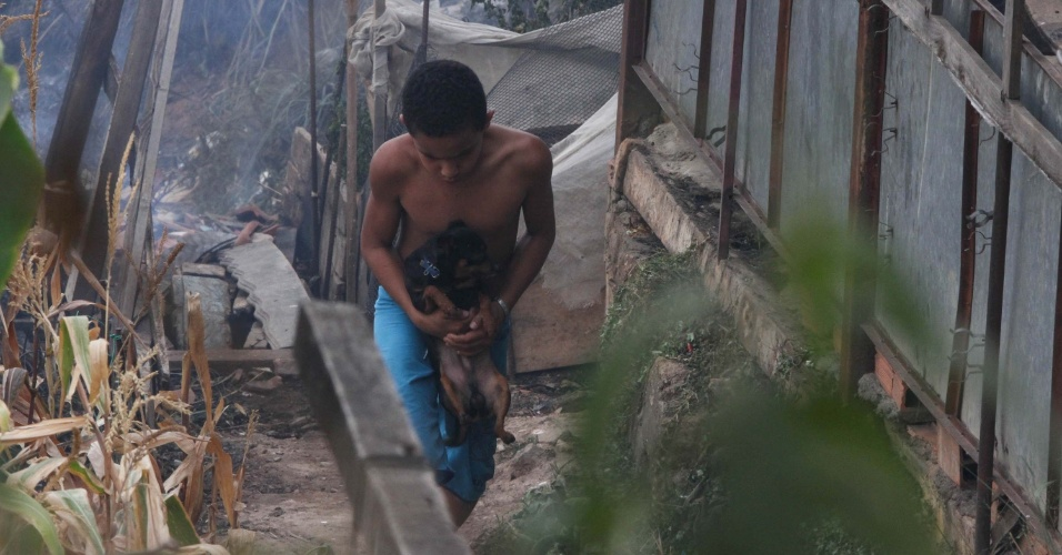 19.set.2012 - Menino salva cachorro de incêndio que atingiu um terreno na rua Vicente de Carvalho, no bairro do Limão em São Paulo (SP). O fogo, que supostamente teria sido iniciado por crianças que brincavam no local, atingiu uma firma e alguns barracos. Ninguém ficou ferido