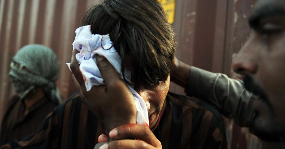 21.set.2012 - Manifestante paquistanês ajuda colega ferido em protesto contra filme anti-Islã, em Islamabad, no Paquistão
