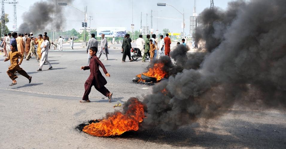 21.set.2012 - Manifestantes paquistaneses queimam pneus e bloqueiam rodovia com barricada durante protesto contra filme anti-islã, em  Rawalpindi