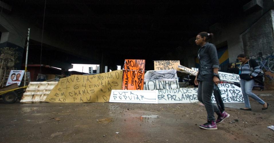 21.set.2012 - Mulheres passam em frente ao bloqueio de uma das entradas da Favela do Moinho, localizada na região central de São Paulo. A barreira foi construída pelos moradores após confronto com agentes da Guarda Civil Metropolitana