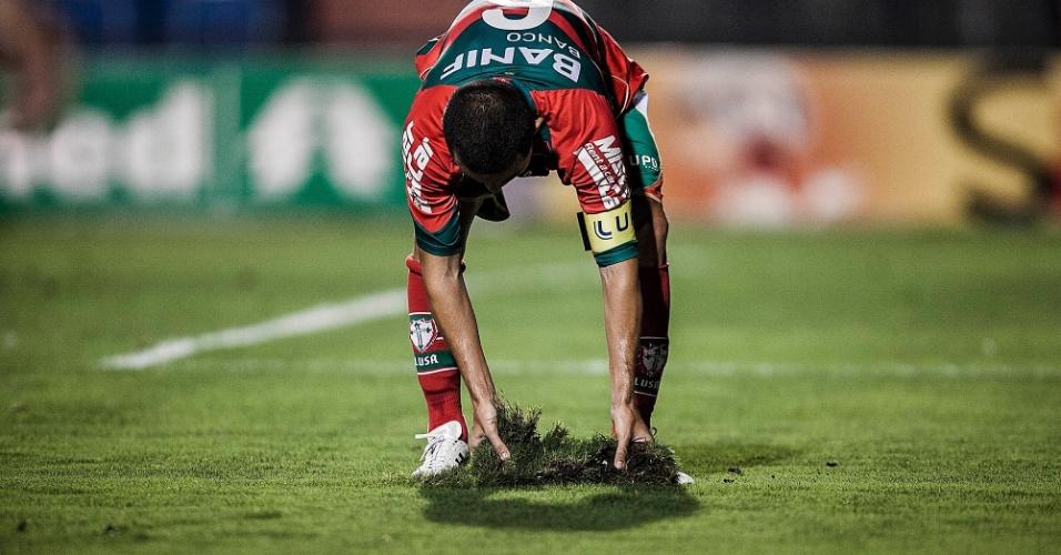 Marcelo Cordeiro, lateral e capitão da Lusa, tenta repor tufo de grama arrancado do chão do Pacaembu