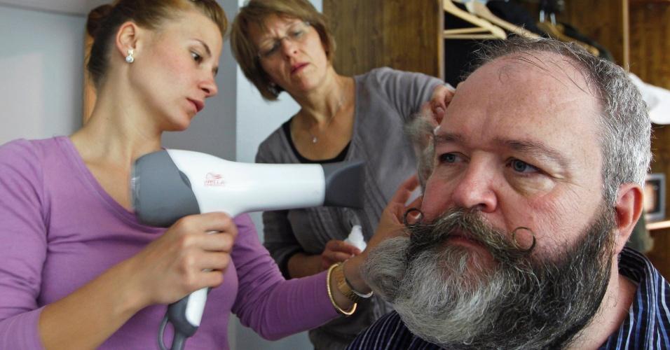 22.set.12 - O cabeleireiro alemão Elmar Weisser, 48, recebe ajuda da mulher, Monica (ao centro), e da amiga Jessica para arrumar a barba para a competição francesa