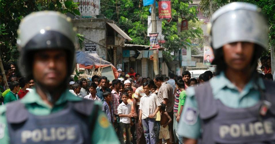 """23.set.2012 - Curiosos observam, próximo a policiais, protesto contra o filme """"Inocência dos Muçulmanos"""", produção norte-americana considerada ofensiva ao profeta Maomé, neste domingo (23), em Dhaka (Bangladesh)"""