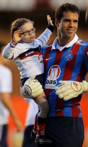 O goleiro do Bahia, Marcelo Lomba entra em campo com uma criança antes da partida contra o Internacional, em Porto Alegre