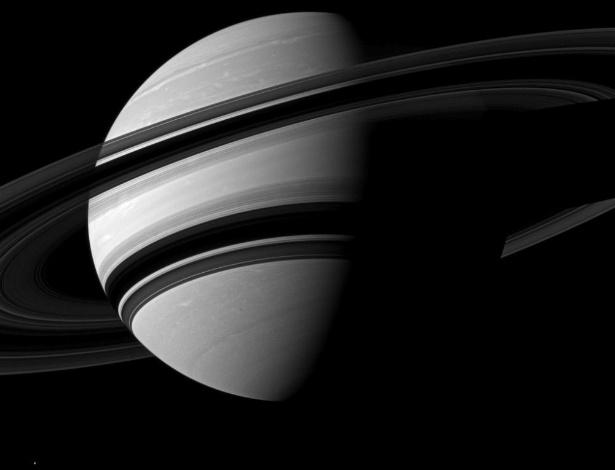 24.set.2012 - A Nasa (Agência Espacial Norte-Americana) divulgou nesta segunda-feira (24) nova imagem de Saturno - o registro foi feito em junho passado pela sonda Cassini. Devido à inclinação, boa parte do gigante ficou escondido e os anéis do planeta criaram sombras no seu hemisfério sul. Além disso, a lua Enceladus, uma das 30 que estão na sua órbita, aparece como um pequeno ponto brilhante no canto esquerdo da fotografia