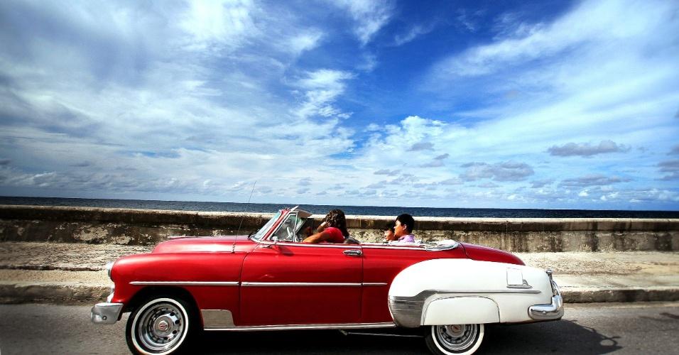24.set.2012 - Casal de turistas asiáticos viaja em um velho conversível pela avenida costeira de Havana, Cuba