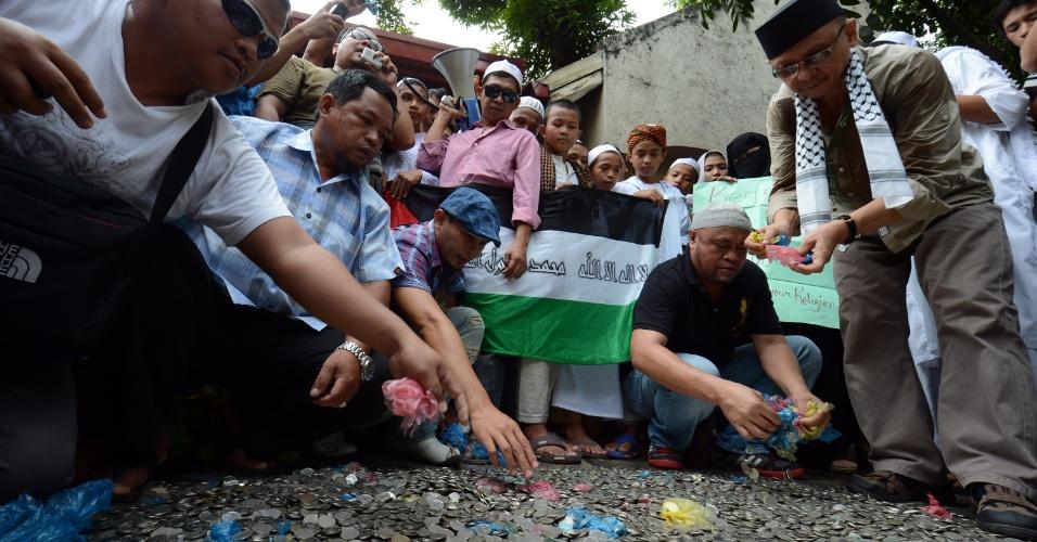 24.set.2012 - Manifestantes recolhem moedas arrecadadas em campanha para que o vídeo considerado anti-Islã seja retirado da internet, nas Filipinas