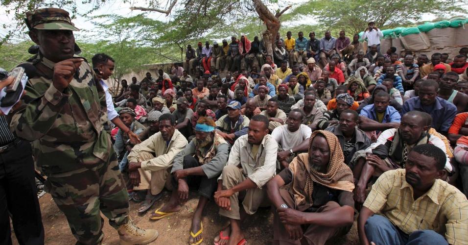 24.set.2012 - Membros do grupo rebelde Al Shabab, que é ligado à Al Qaeda, escutam soldado somali após terem se rendido às autoridades da Somália, na capital do país, Mogadício