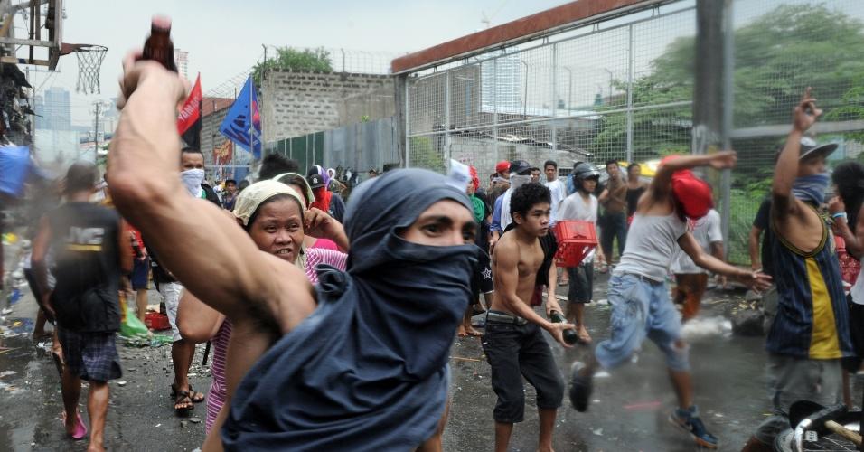 24.set.2012 - Moradores atiram pedras e garrafas em equipe de demolição e antimotim da polícia em área habitada ilegamente no distrito de Makati, nas Filipinas