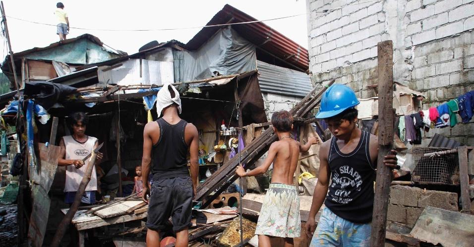 24.set.2012 - Moradores reúnem buscam pertences em casa que foi destruída após tornado que atingiu Quenzon, em Manila (Filipinas). Cerca de 50 casas fora danificadas, segundo a imprensa local