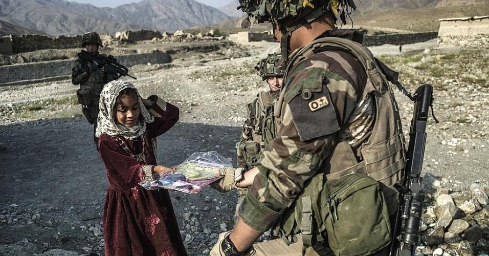 24.set.2012 - Soldado francês entrega pipa para criança afegã nos arredores Naghlu, perto da base militar da França no Afeganistão