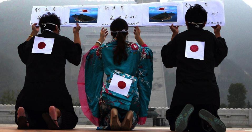 """24.set.2012 - Vestindo trajes típicos, manifestantes chineses se ajoelham diante de imagem de Buda com bandeira onde se lê """"Diaoyu pertente à China"""", em Lushan, na província chinesa de Henan"""