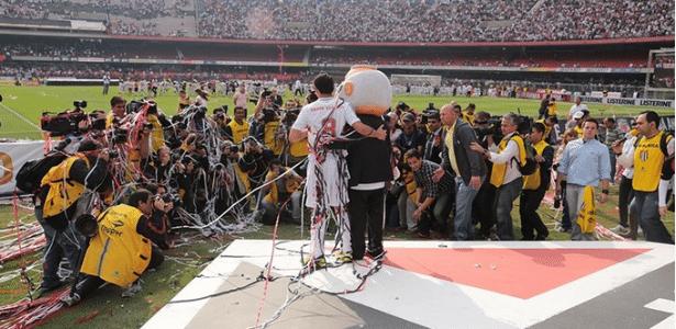 Ganso e a mascote do São Paulo são cercados por dezenas de fotógrafos na apresentação do meia