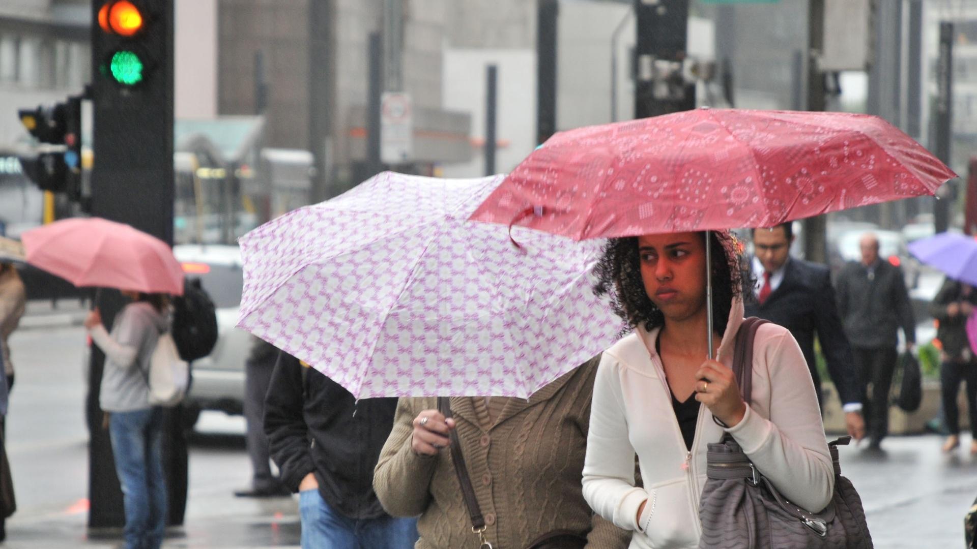 26.set.2012 - Mulher se protege da chuva e do frio na avenida Paulista, em São Paulo, onde os termômetros chegaram a registrar 9°C. Com os ventos, a sensação térmica chegou a -0,5°C por volta do meio-dia