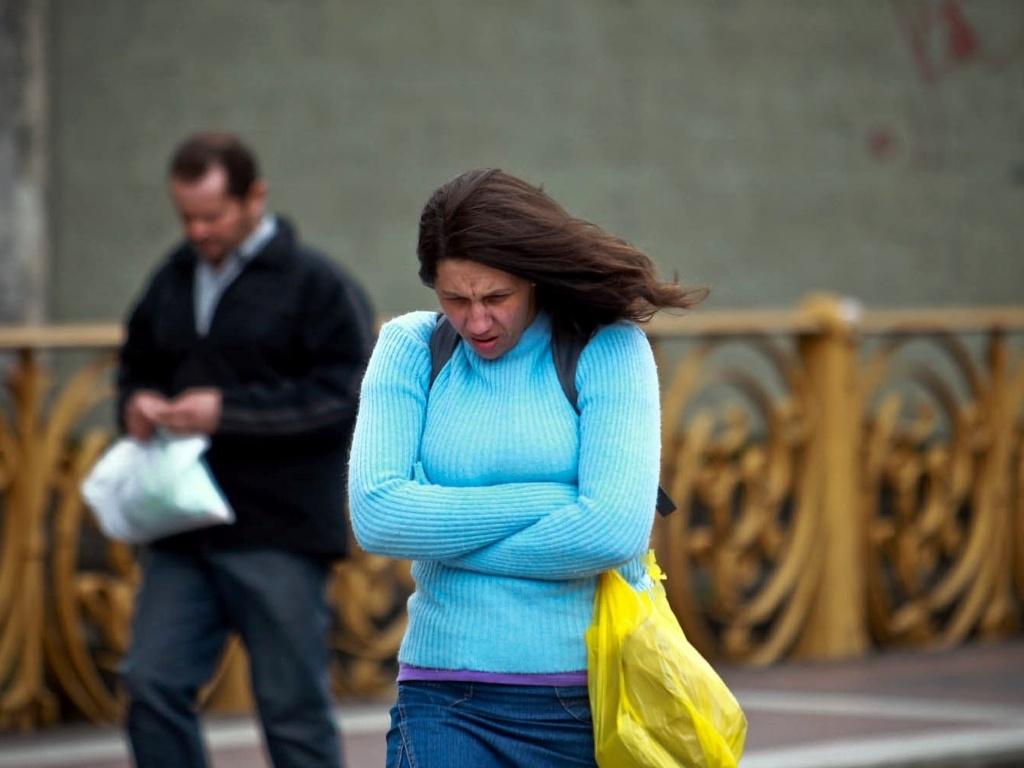 26.set.2012 - Mulher se protege de frio em São Paulo, onde os termômetros chegaram a registrar 9°C. Com os ventos, a sensação térmica chegou a -0,5°C