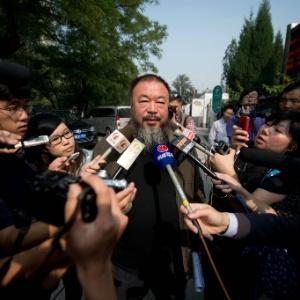27.set.2012 - Ai Weiwei, dissidente e artista chinês responde a perguntas de jornalistas estrangeiros do lado de fora de um tribunal em Pequim, na China, nesta quinta-feira (27) - Ed Jones/AFP