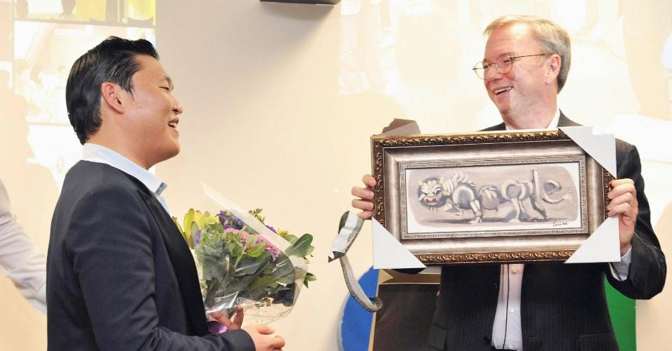 27.set.2012 - Eric Schmidt (direita), presidente do Google, presenteia o cantor sul-coreano Psy (esquerda) com um quadro de um Doodle, desenhos utilizados na página inicial do buscador para homenagear alguma data especial ou alguma personalidade. O executivo da companhia americana estava na Coreia do Sul para lançar o tablet Nexus 7