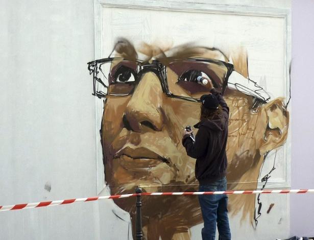 Grafiteiro pinta rosto de morador do centro de Paris em muro da cidade (22/9/12) - EFE