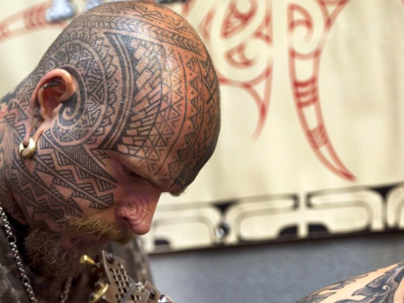 28.set.2012 - Tatuador Matt Black trabalha no braço de um dos clientes durante o oitavo London International Tattoo, convenção realizada no Tobacco Dock, região leste de Londres de hoje à domingo (30)