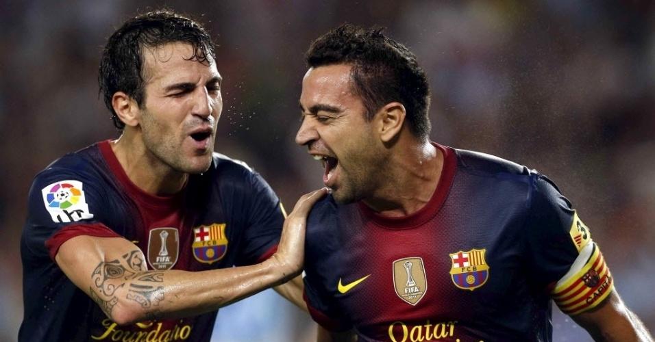 Fábregas e Xavi comemoram gol do Barcelona contra o Sevilla