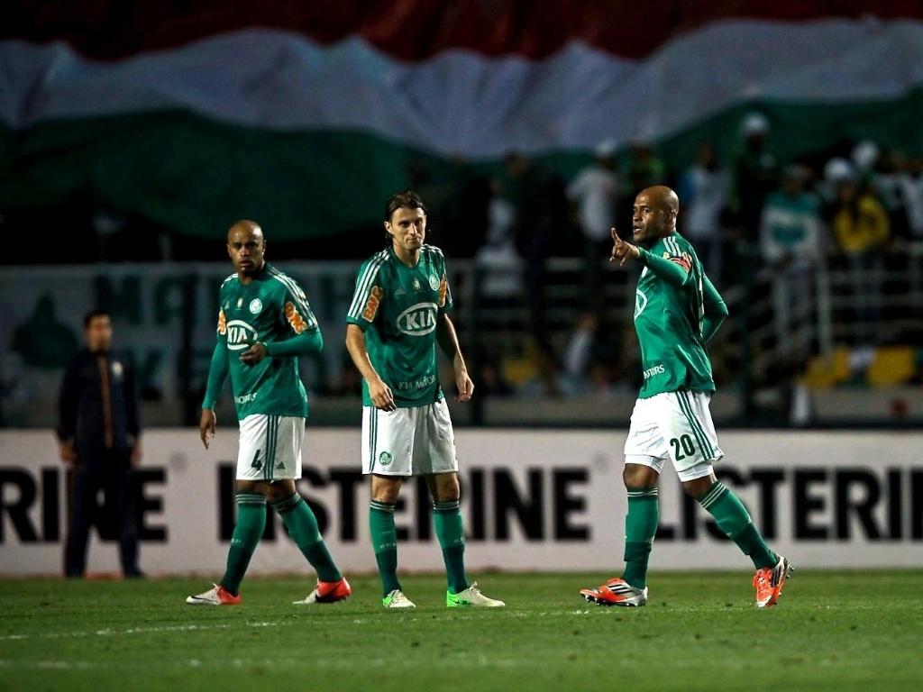 Jogadores do Palmeiras conversam durante partida; ao fundo, torcida abre o bandeirão