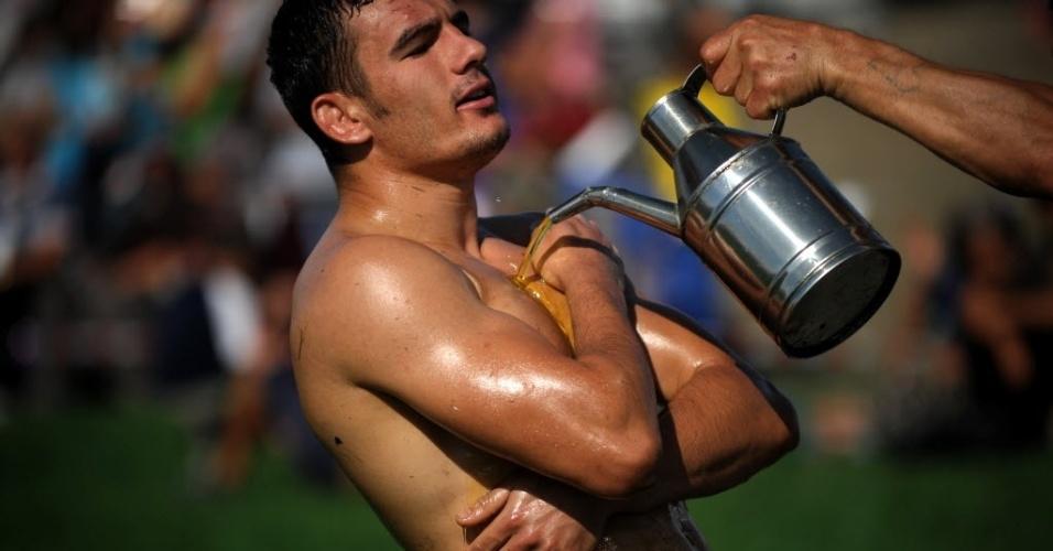 Competidor é encharcado de óleo antes de combate pela luta olímpica com óleo, na Bulgária