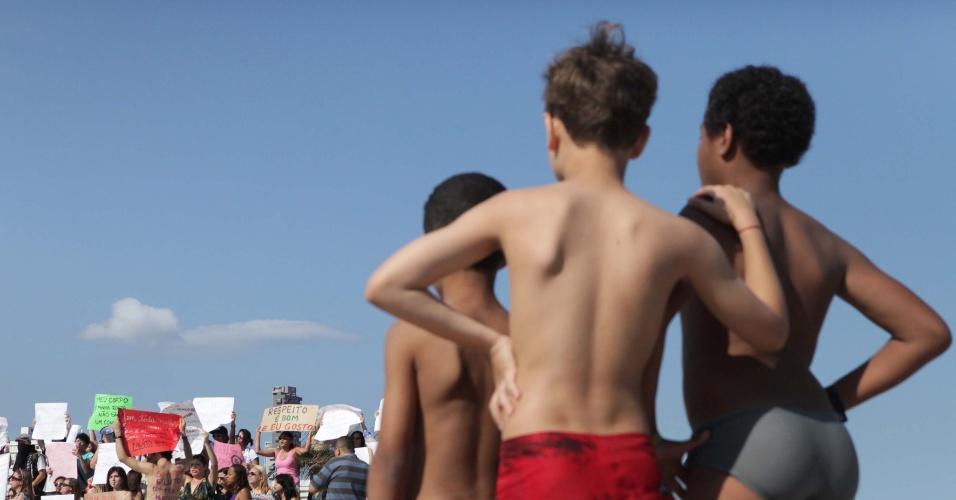 Crianças observam passagem da Marcha das Vadias, em Santos (SP)