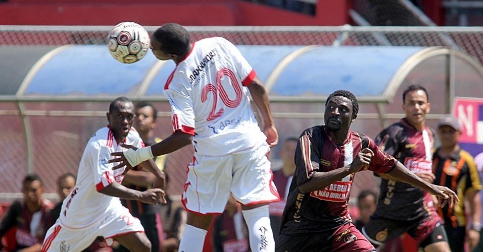 Jogador do Classe A (branco) cabeceia a bola durante partida contra o Juventus (vinho)