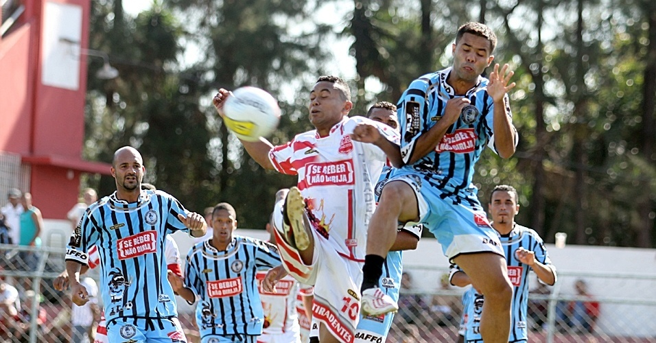 Jogador do Tiradentes (de branco) tenta chegar à bola em meio à defesa do Baffo (azul)