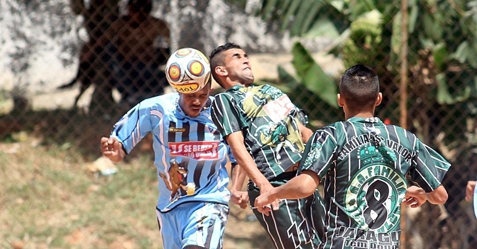 Jogadores do Novo Roma (de azul) e do Familika 100 valor (verde) disputam a bola