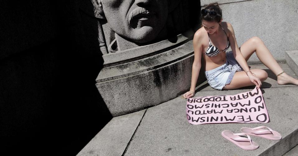 Mulher finaliza cartaz para uso na Marcha das Vadias em Santos (SP)