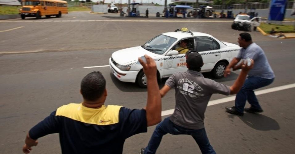 1°.out.2012 - Grupo de manifestantes joga sacos plásticos cheios de água em um táxi de Manágua, Nicarágua , por causa da paralisação dos taxistas, que reivindicam melhorias na  política do governo sobre os combustíveis no país